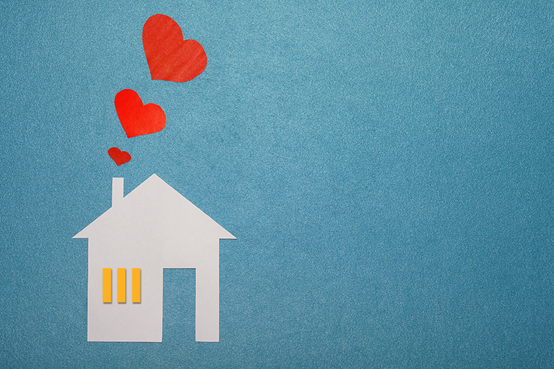 Paper cut out of a house with three hearts