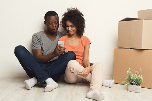 Couple sitting on floor with moving boxes and looking at a mobile phone