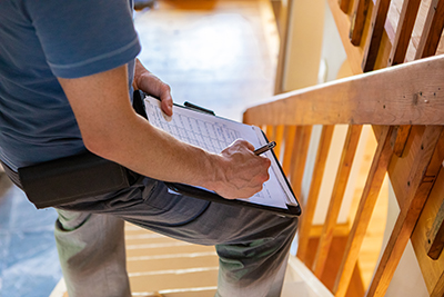 Man holding checklist in constructed home