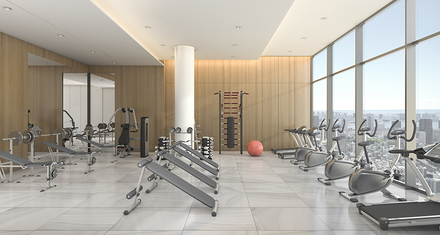Condominium gym with various gym equipment overlooking a skyline