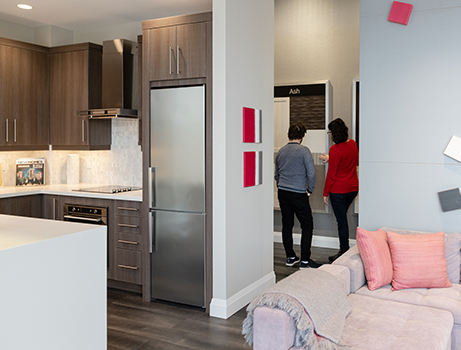 Two people looking at finishings in a condo sales centre