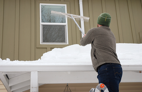 Man on ladder raking snow off rooftop