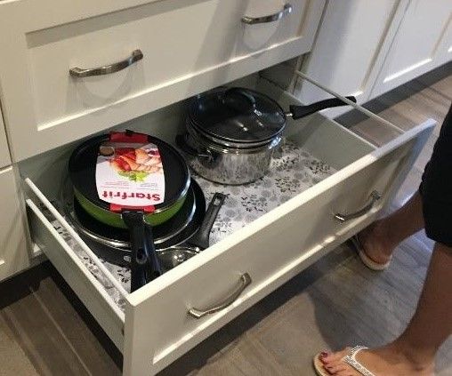 Pulled open kitchen drawer with pots and pans within it